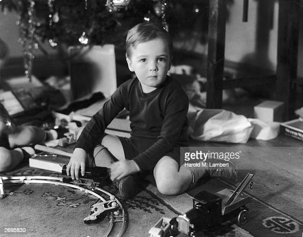 A young boy playing with a toy truck and a model train set while sitting under a Christmas tree