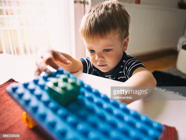 Young boy playing with colored building blocks