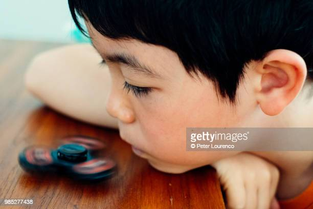 Young boy playing with fidget spinner