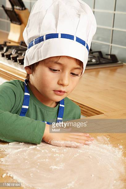 Young boy playing with flour on tabletop
