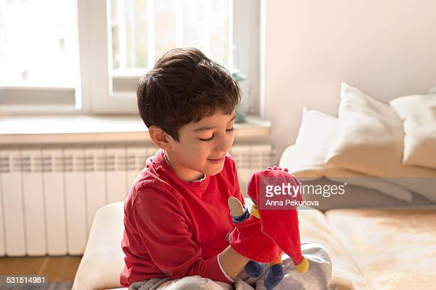 Young boy playing with hand puppet
