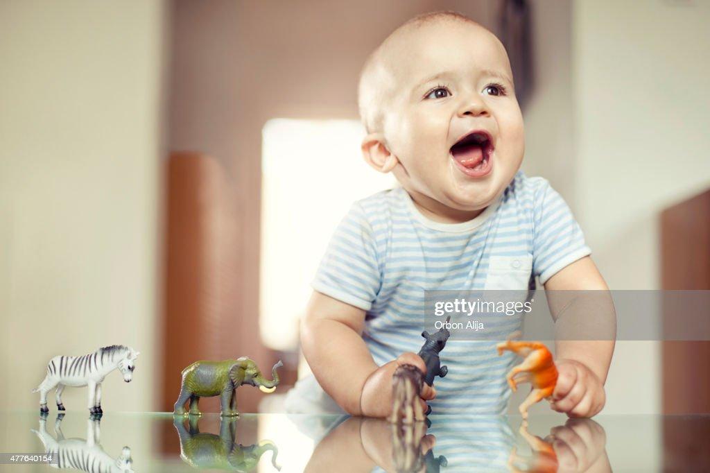 Jovem rapaz a brincar com brinquedos de animais : Foto de stock