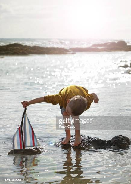 young boy playing with toy boat in the sea - craft stock pictures, royalty-free photos & images