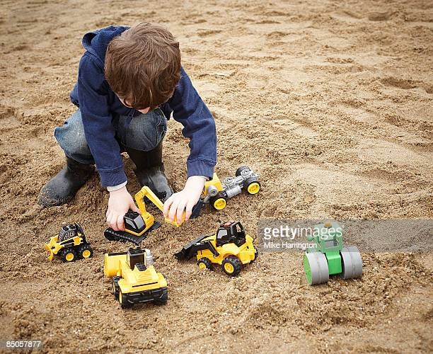 Young boy (3-5yrs) playing with toy diggers in san