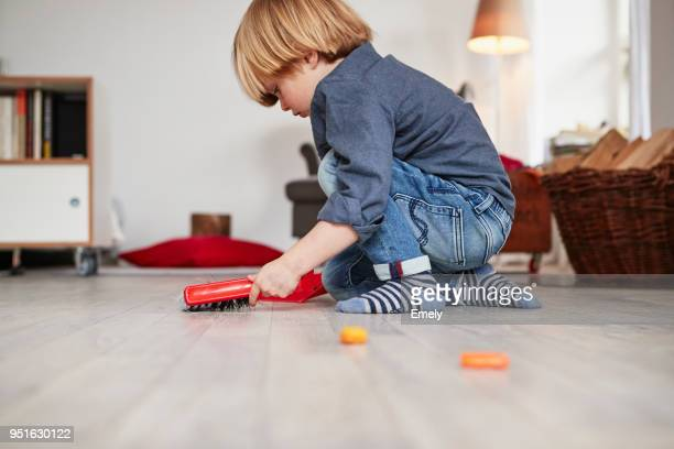 young boy playing with toy dustpan and brush - alleen jongens stockfoto's en -beelden