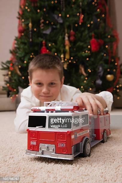 Young boy playing with toy fire truck in front of a Christmas tree