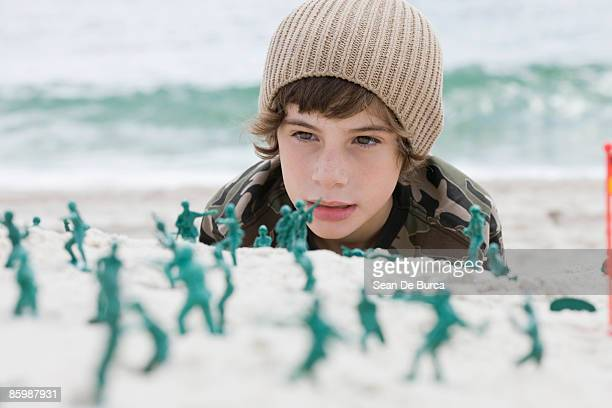 Young boy playing with toy soldiers at beach