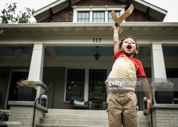 young boy (3 yrs) playing with toy sword in front of house - rough housing stock pictures, royalty-free photos & images