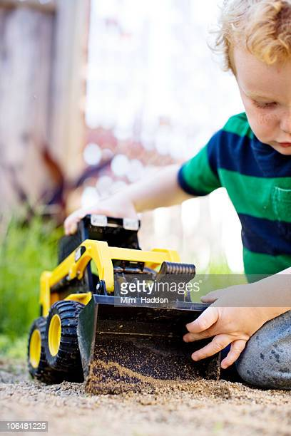 Young Boy Playing with Toy Tractor in Sandbox