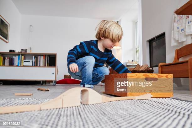 young boy playing with toys in living room, low angle view - nur kinder stock-fotos und bilder