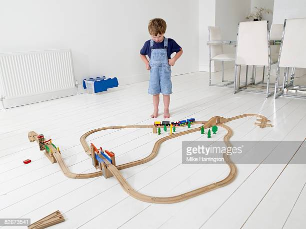 Young boy playing with train track