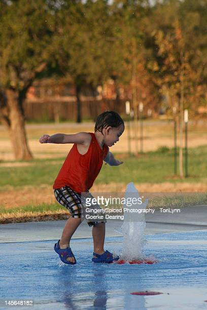 young boy playing with water in park - lynn pleasant stock pictures, royalty-free photos & images