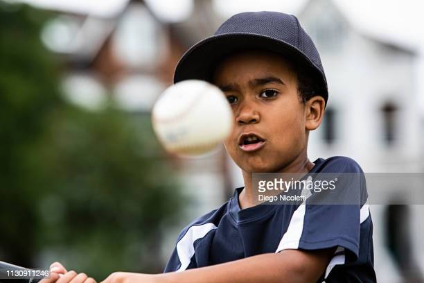 young boy plays baseball, ready to hit the ball - batting sports activity stock pictures, royalty-free photos & images