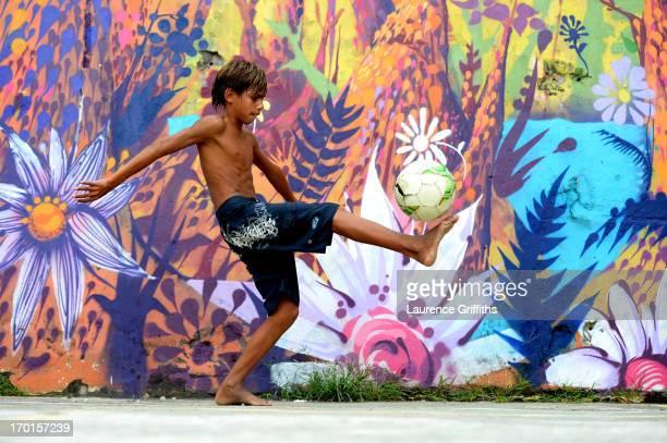 Young boy plays football in a Favela on June 7, 2013 in Rio de Janeiro, Brazil.