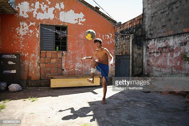 A young boy plays football on streets outside the stadium ahead of the 2014 FIFA World Cup Brazil Group D match between England and Italy at Arena...