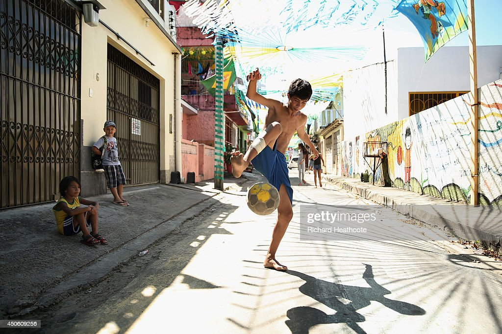 A young boy plays football on streets outside the stadium ahead of the 2014 FIFA World Cup Brazil Group D match between England and Italy at Arena Amazonia on June 14, 2014 in Manaus, Brazil.