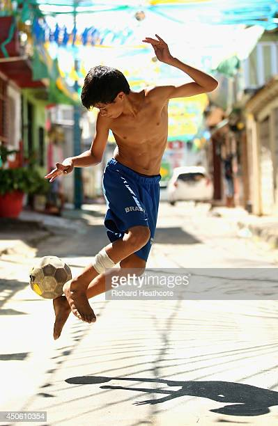 A young boy plays football on the streets outside the stadium ahead of the 2014 FIFA World Cup Brazil Group D match between England and Italy at...