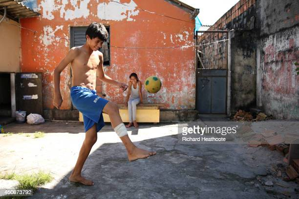 Young boy plays football on the streets outside the stadium ahead of the 2014 FIFA World Cup Brazil Group D match between England and Italy at Arena...