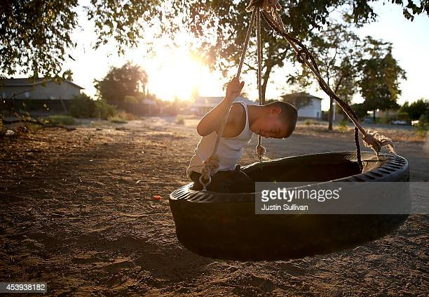 A young boy plays on a tire swing on August 21 2014 in Mendota California As the severe California drought continues for a third straight year...