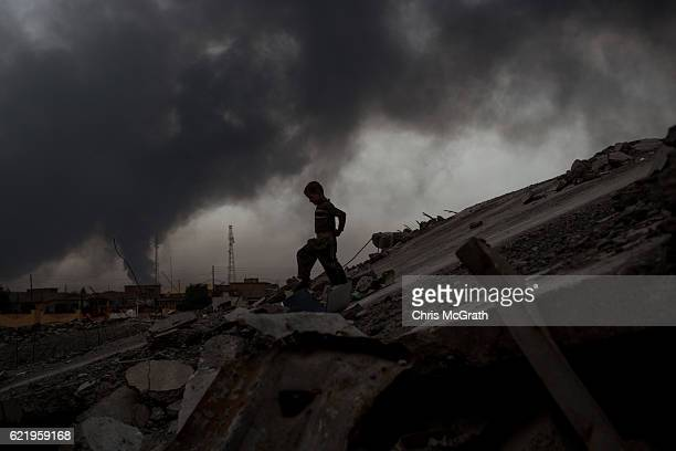 A young boy plays on rubble at a destroyed football stadium as heavy smoke from burning oil wells fills the sky on November 9 2016 in Al Qayyarah...