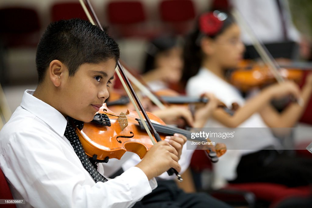 A young boy plays violin and stares outward : Stock Photo
