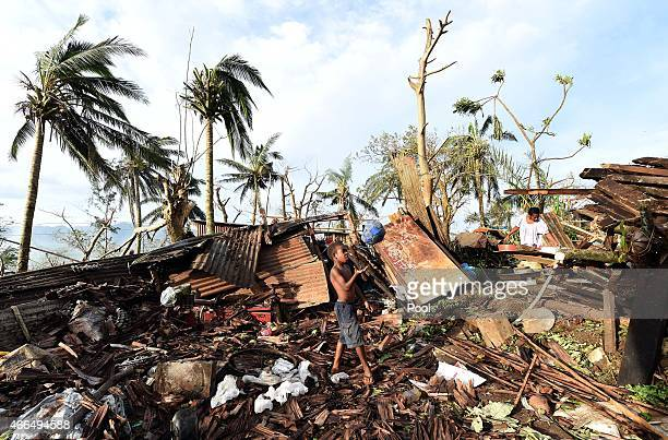 A young boy plays with a ball as his mother searches through the ruins of their family home on March 16 2015 in Port Vila Vanuatu Cyclone Pam has hit...
