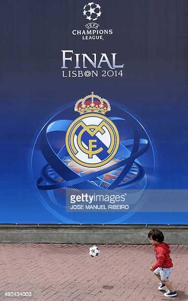 A young boy plays with a ball in front of a banner with the logo of the Real Madrid Football Club announcing the upcoming UEFA Champions League final...