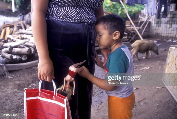 A young boy plays with a barbie doll as he leans on his mother in Juchitan Mexico October 1 2002 In the southern Mexican town of Juchitan of roughly...