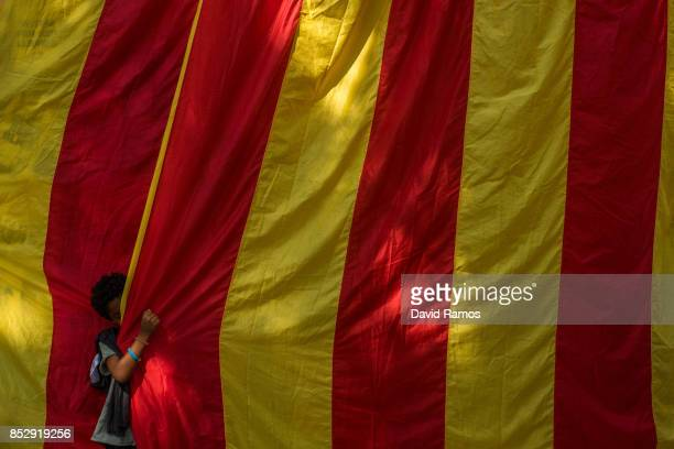 A young boy plays with a Catalan flag during a Catalan ProIndependence meeting on September 24 2017 in Barcelona Spain Spain's government announced...