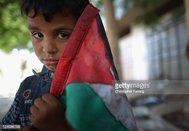 Young boy plays with a Palestinian flag in a street in Rafah near to the Egyptian border on August 21, 2011 in Rafah, Gaza. Palestinian President...