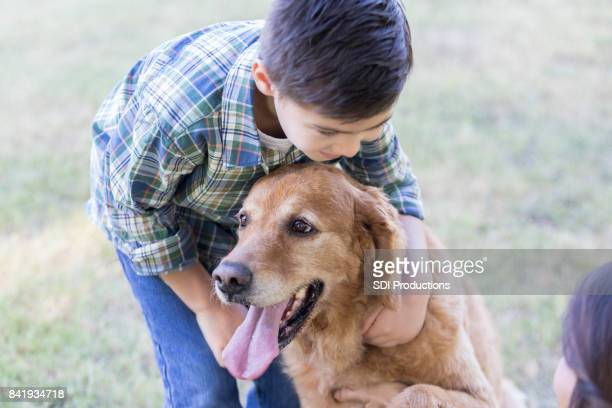 Young boy plays with his dog in an open field