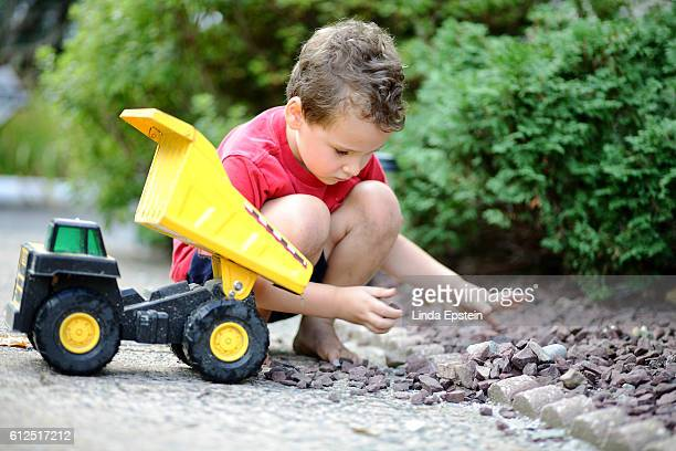 Young boy plays with his toy dump truck