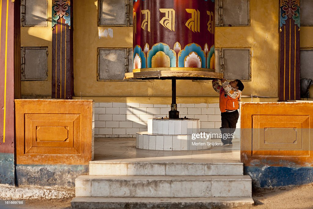 Young boy plays with prayer wheel : Stockfoto