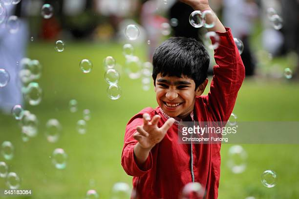 A young boy plays with soap bubbles as the Birmingham Muslim community celebrate the festival of Eid in Small Heath Park on July 6 2016 in Birmingham...