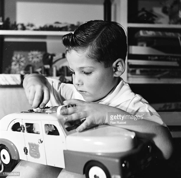 A young boy plays with toy car cab 1948