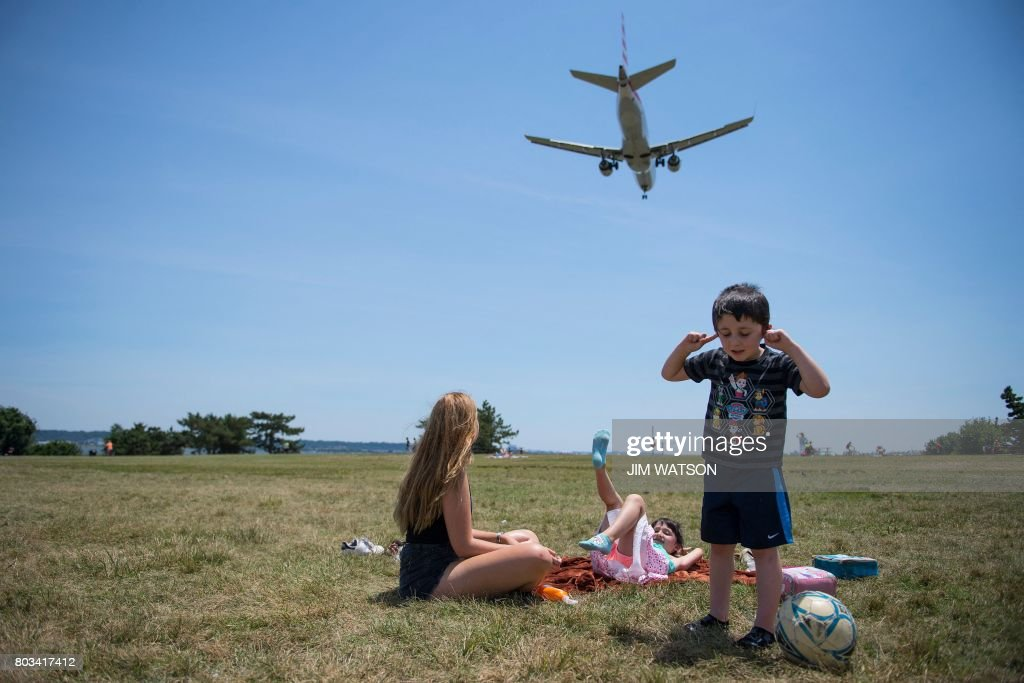 A young boy plugs his ears as his sister (C) and nanny (L) watch from Gravelly Point Park as planes land at Ronald Reagan National Airport in Arlington, Virginia on June 29, 2017. - President Donald Trump's travel ban on people from six mostly Muslim countries will come into force late Thursday, as controversy swirls over who qualifies for an exemption based on family ties.