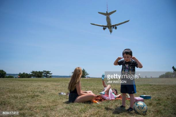 A young boy plugs his ears as his sister and nanny watch from Gravelly Point Park as planes land at Ronald Reagan National Airport in Arlington...