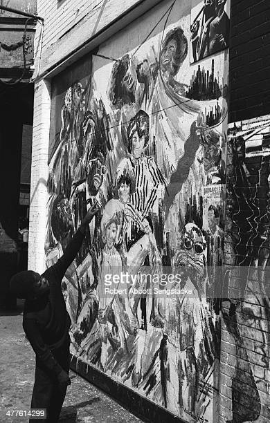 Young boy points to one of the figures painted on the 'Wall of Respect' mural , Chicago, Illinois, 1968.
