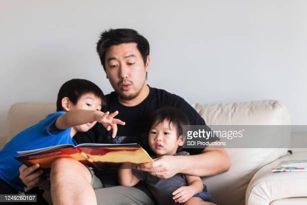 若い男の子は、お父さんが声に出して読んでいる物語の本を指しています - 主夫 ストックフォトと画像
