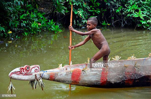 A young boy poling a traditional canoe Asmat region Papua Province Indonesia