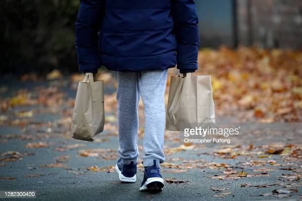 Young boy poses as he carries free half-term meal packs for himself and his sibling from the Watering Can Cafe on October 26, 2020 in Liverpool,...