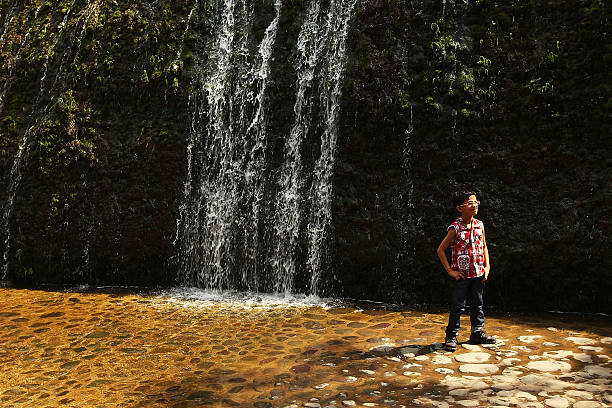 A young boy poses for a photo in front of a waterfall at the Rock Garden on March 26 2010 in Chandigarh India The 12acre Rock Garden which began as...