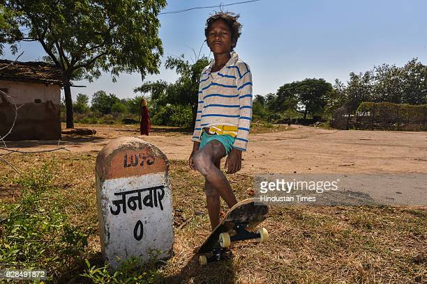 Young boy poses with his skateboard near Zero milestone of village on October 26, 2016 in Janwaar, India. Thanks to a German community activist and...