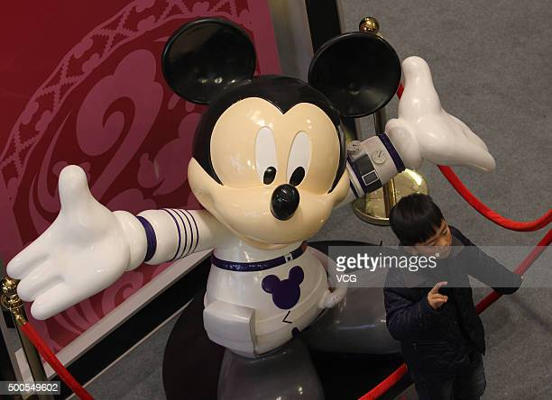 A young boy poses with Mickey Mouse displayed at CapitaMall 1818 on December 5 2015 in Wuhan Hubei Province of China Disney Characters exhibition was...