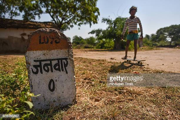 Young boy poses with their skate boards near Zero milestone of village on October 26, 2016 in Janwaar, India. Thanks to a German community activist...