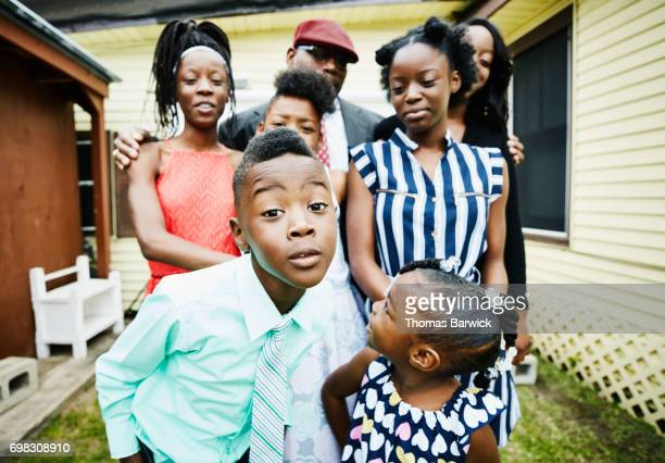 young boy posing for portrait with family members in front of house - funny black girl stock photos and pictures
