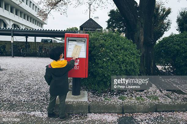 young boy posting a letter - sending stock photos and pictures