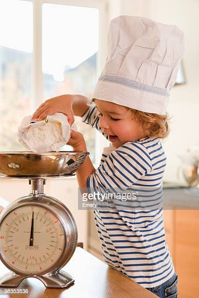 young boy pouring flour onto scale - コック帽 ストックフォトと画像
