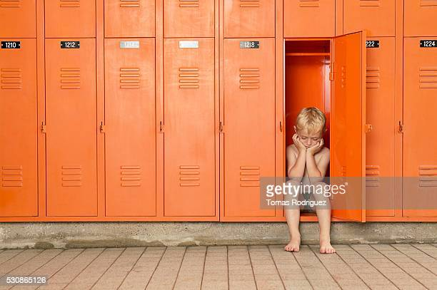 Young boy pouts in locker room