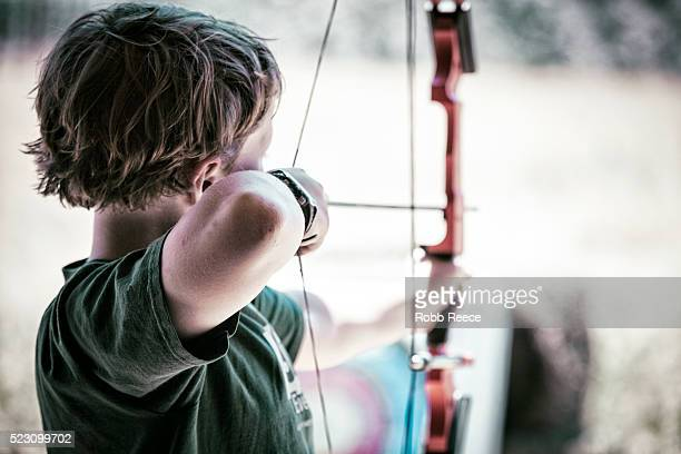 a young boy practices archery at camp in colorado - robb reece stock-fotos und bilder